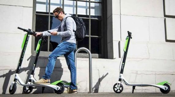 man next to an escooter