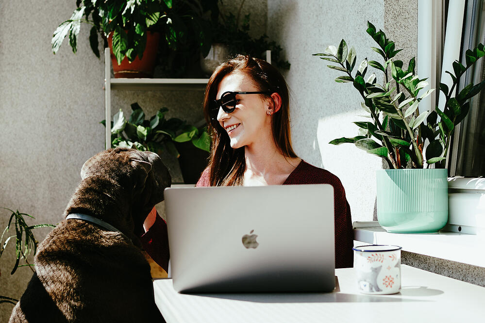 Girl with a dog working on laptop