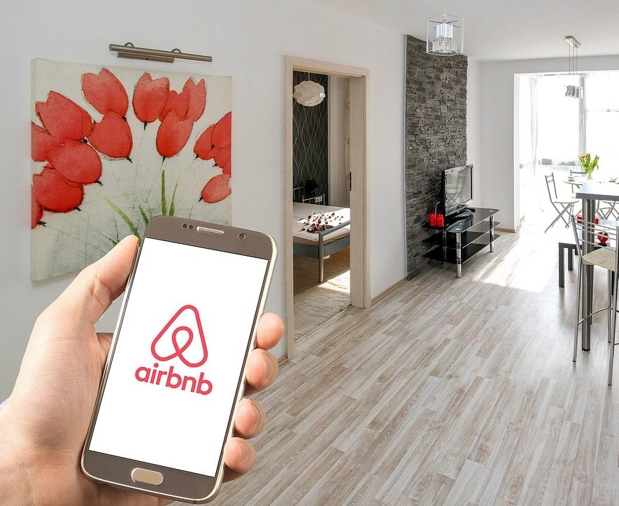 Man holding a mobile phone with airbnb app