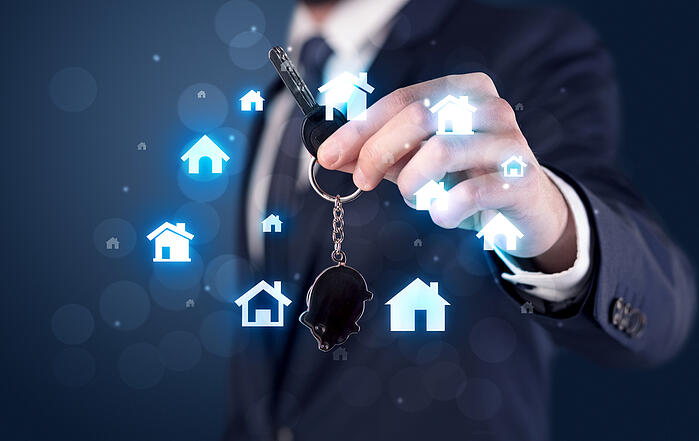 Man holding keys with house graphics around and dark background