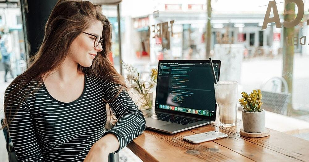 a woman looking at the code on the screen sitting in a restaurant